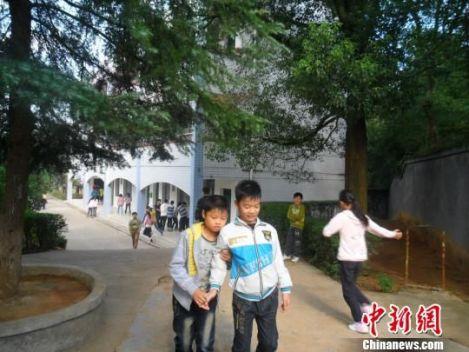 4年来,13岁的余兴泉(左一)每天都搀扶着腿脚不便的同学左臣进出教室、食堂和厕所。 李俊杰 摄