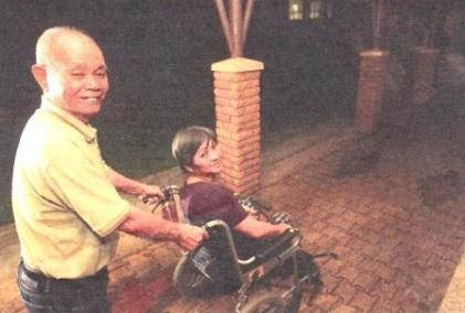 高龄79岁的招柱每周一推着62岁的残障女邻居梁志平下楼,等救护车送她到医院做物理治疗,回来后再推她上楼。(邬福梁摄)