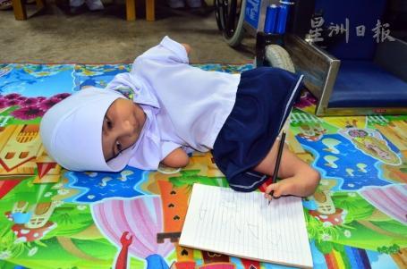 努达米雅用脚指夹着铅笔工整地写出自己的名字。(图:星洲日报)