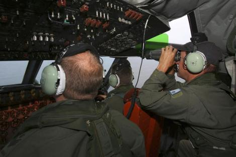 Flight Engineer Ron Day, right, on board a Royal Australian Air Force AP-3C Orion, searches for the missing Malaysia Airlines Flight 370 in the southern Indian Ocean. (AP)