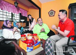 """谢天成(右一)和黄清清(右三)拿了农历新年糕饼去探访他们所""""领养""""的巴哈隆(右二)一家。巴哈隆的母亲(左一)和太太也一起提早向两人拜年。(熊俊华摄)"""