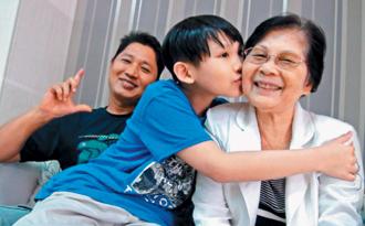 11歲男童鄭浚翔抗癌重生,他摟著78歲的奶奶,圖左為鄭浚翔的父親鄭武傑。(联合报記者王慧瑛/攝影)