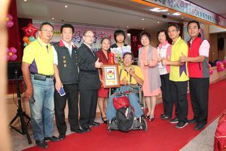 王惠贞(左4)在先生(坐轮椅者)鼓励下投入志工,今天获桃园市好人好事表扬,市长苏家明(左3)大力称讚夫妻都是好榜样。记者郑国樑/摄影