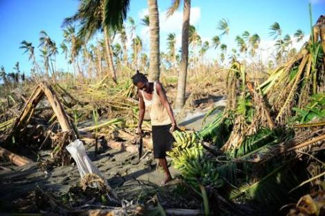 A women carries a bunch of bananas she found on the banks of the Noai river, outside of Vanuatu's capital Port Vila on March 21, 2015 after Cyclone Pam ripped through the island nation. (Photo By Jeremy Piper/AFP)