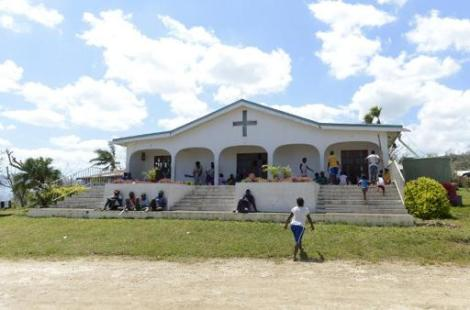 People take shelter at the Apostolic Church of Tagabe in Port Vila on March 20, 2015 after Cyclone Pam devastated Vanuatu. (Photo By Fred Payet/AFP)