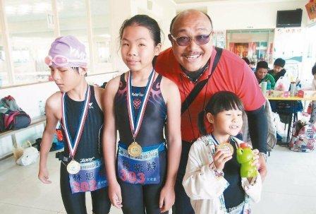 三名天生全盲的小朋友杨紫羚(左二)、林思嘉(左一)及梁瑜涵(右一),在教练陈绍璋(右二)指导下,顺利完成三铁比赛,拿着奖牌开心合照。 记者程远述/摄影