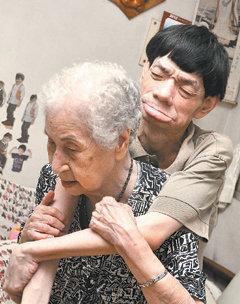 88岁妇人许林密(左)独自扶养罹患重度身心障碍的小儿子许庭福长大,将儿子背上背下,每月还捐款做善事,获选为南区区公所慈晖妈妈。(记者庄宗勋/摄影)