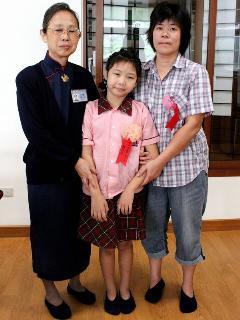 就读嘉义县梅山国小3年级女童蔡芳欣(中),小小年纪就罹患骨癌,但她并未被命运击倒努力向学,30日获颁「慈济新芽奖学金」。 图右为蔡芳欣的母亲康玉凤。 (慈济基金会提供)