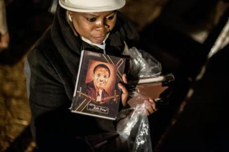 A South African worshipper holds a book bearing a portrait of Benedict Daswa as she attends a vigil in Thohoyandou, on the eve of his beatification ceremony on on September 12, 2015. (Photo By Marco Longari, AFP)