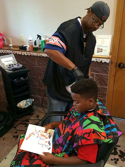 Courtney Holmes gives haircuts to kids who read to him at Back to School Bash in Dubuque, Iowa COURTESY ANDERSON SAINCI