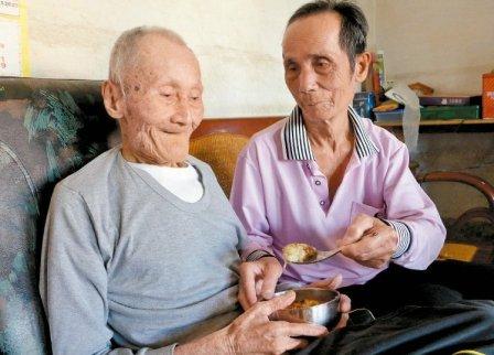 78岁张松柏(后)照顾94岁李火炉生活起居,过去都会一起吃年夜饭。