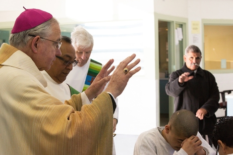 "Archbishop José H. Gomez blesses and prays over a youth in the high-security ""Compound"" at the Barry J. Nidorf Juvenile Hall in Sylmar. (photo/Victor Aleman)"