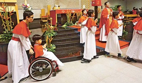 Jeremiah Liauw, 10, being helped around in his wheelchair during his first Mass as an altar server.