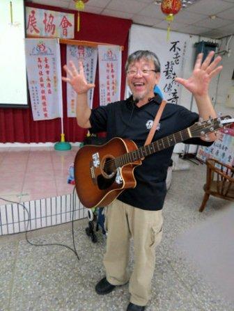 李若望神父教导社区老人乐器,并以吉他伴奏演出。(记者周宗祯/摄影)