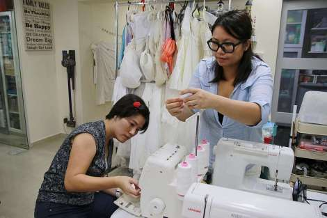 Businesswoman Andrea Toh, 42, one of the founders of Angel Gowns Singapore, and housewife Angelyn Yii, 34, deconstruct donated gowns and repurpose them into smaller outfits suitable for babies.ST PHOTOS: NIVASH JOYVIN