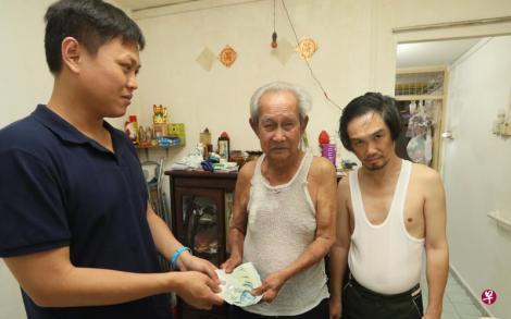 记者把好心人捐赠的2000元交给林文福一家。(吴伟国摄影)