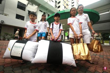 林慧恩(右二)和爸爸林伟记(右一)、妈妈冯雪玲(左二)拿粥,弟弟林乐奇(左一)和姚佳言拿枕头,准备送去受惠者家。(邬福樑摄)