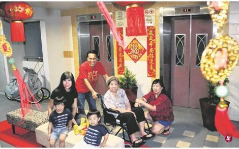 哈姆扎(红衣男)为了给让邻居间有一起过节的感觉,今年农历新年将电梯间和走廊特别布置了一番。(庄耿闻摄影)