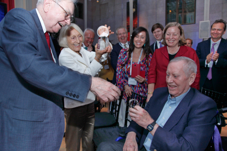 Chuck Feeney '56, right, receives the Forbes 400 Lifetime Achievement Award for Philanthropy, along with a watch, from Warren Buffett (who is the award's only previous recipient) June 17 in New York City. Feeney's wife Helga, at left, is holding the award.