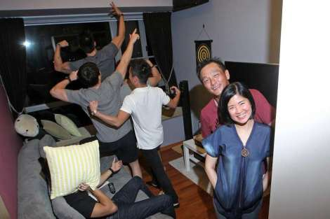 Mr Francis Ng (right) and his wife Joyce Tan have converted a room in their new apartment - which had been meant for their son Darren - into an entertainment centre for troubled young people. The couple have become akin to foster parents for 30 or so at-risk youth. Darren was hacked to death in a gang fight in 2010.ST PHOTO: CHEW SENG KIM ST PHOTO: NEO XIAOBIN